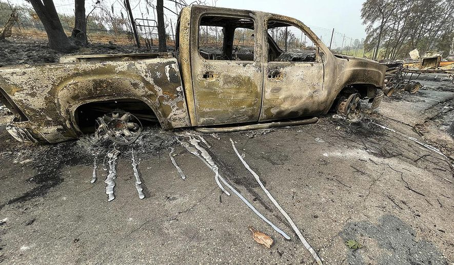 The melted metal from a pickup truck's rims ran down the driveway of this Chicago Park home after the River Fire burned through here Saturday, Aug. 7, 2021. About a two-hour drive south from the Dixie Fire, crews had surrounded nearly half of the River Fire that broke out Wednesday near the town of Colfax and destroyed 68 homes and other buildings. Evacuation orders for thousands of people in Nevada and Placer counties were lifted Friday. (Elias Funez/The Union via AP)