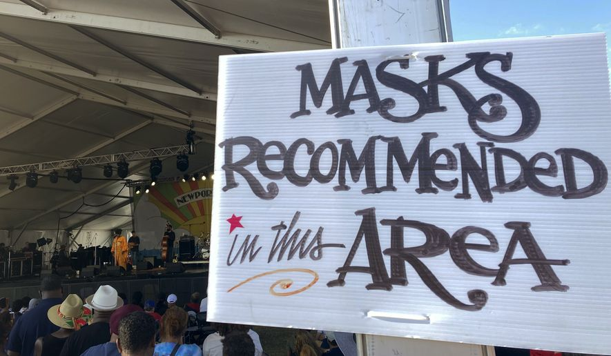 In this July 31, 2021, file photo, a sign recommends attendees of the Newport Jazz Festival wear masks in a tented area where singer Ledisi performs in Newport, R.I. Festival-goers were also required to digitally upload proof of COVID-19 vaccination or a recent negative test. (AP Photo/Matt O'Brien, File)