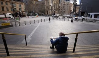 A man reads a newspaper on the steps of Flinders Street Station in Melbourne, Australia, Wednesday, Aug. 11, 2021. Australia's second-largest city has extended its lockdown in a bid to eliminate COVID-19 while authorities in Sydney flagged restrictions easing for vaccinated residents despite the delta variant continuing to spread. (AAP Image/Daniel Pockett)