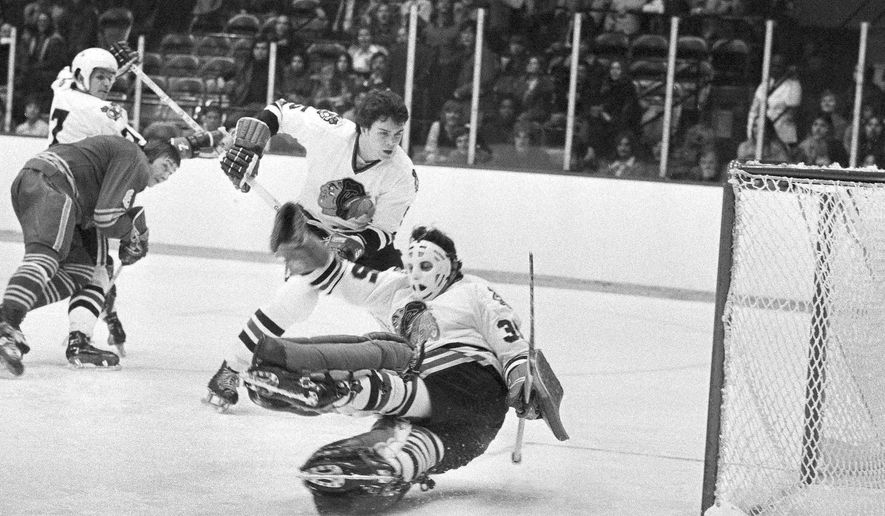 In this Dec. 19, 1973, file photo, Chicago Blackhawks goalie Tony Esposito (35) stops a Buffalo Sabres shot during the first period of an NHL hockey game in Chicago. Chicago's Phil Russell (5) watches as Buffalo's Jim Lorentz (8) keeps Chicago's Pit Martin (7) out of the play. Esposito, a Hall of Fame goaltender who played almost his entire 16-year career with the Blackhawks, has died following a brief battle with pancreatic cancer, the team announced Tuesday, Aug. 10, 2021. He was 78. (AP Photo/Fred Jewell. File) **FILE**