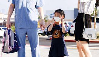 Elena Choi puts on her mask as she starts kindergarten on the first day of school at the new Hannah Marie Brown Elementary School in Henderson, Nev., Monday, Aug. 9, 2021. Doors opened Monday at schools in and around Las Vegas, where masks were required for the more than 300,000 students and about 18,000 teachers returning to in-person classes at the fifth-largest district in the nation. (Yasmina Chavez/Las Vegas Sun via AP)