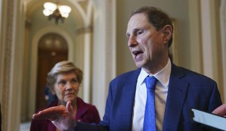 In this July 21, 2021, photo Sen. Ron Wyden, D-Ore., chair of the Senate Finance Committee, joined at left by Sen. Elizabeth Warren, D-Mass., talks about their discussions on the national debt with Senate Majority Leader Chuck Schumer, D-N.Y., at the Capitol in Washington. (AP Photo/J. Scott Applewhite) **FILE**