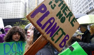 Demonstrators wave their protest signs during a climate march in downtown Chicago on April 29, 2016, assembled to protest U.S. environmental policies. (AP Photo/Nam Y. Huh) **FILE**