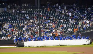 The grounds unrolls the tarp during a rain delay before a baseball game between the New York Mets and the Washington Nationals, Wednesday, Aug. 11, 2021, in New York. (AP Photo/Mary Altaffer)