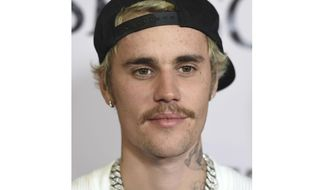 """FILE - In this Jan. 27, 2020, file photo, Justin Bieber arrives at the Los Angeles premiere of """"Justin Bieber: Seasons."""" Justin Bieber leads this year's list of nominees at the 2021 MTV Video Music Awards, followed closely by Megan Thee Stallion, Billie Eilish, BTS, Doja Cat, Drake, Giveon, Lil Nas X and first-time nominee Olivia Rodrigo.Bieber has seven nods, including video of the year and best direction for """"POPSTAR,"""" artist of the year, best cinematography for """"Holy"""" and best pop song, best editing and best collaboration for """"Peaches.""""  (Photo by Jordan Strauss/Invision/AP, File)"""