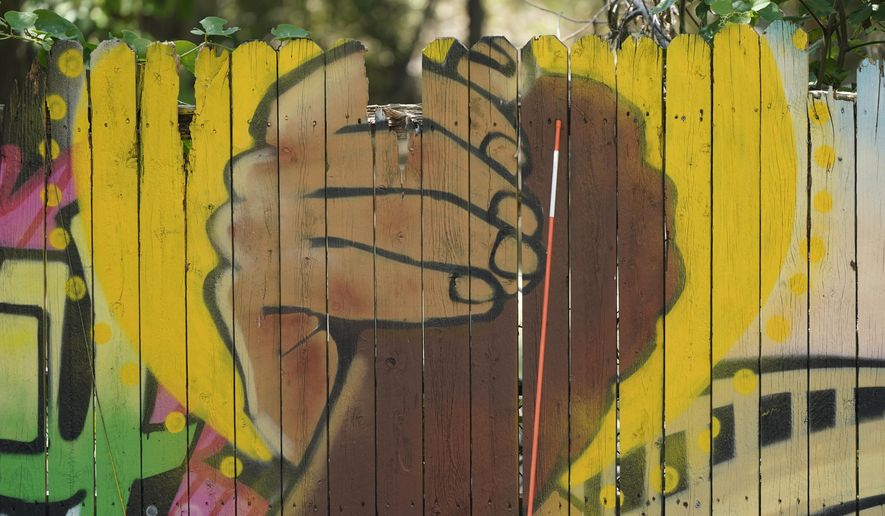 A mural on a fence is displayed at United Fort Worth, a grassroots community organization in Fort Worth, Texas, Tuesday, Aug. 10, 2021. (AP Photo/LM Otero).