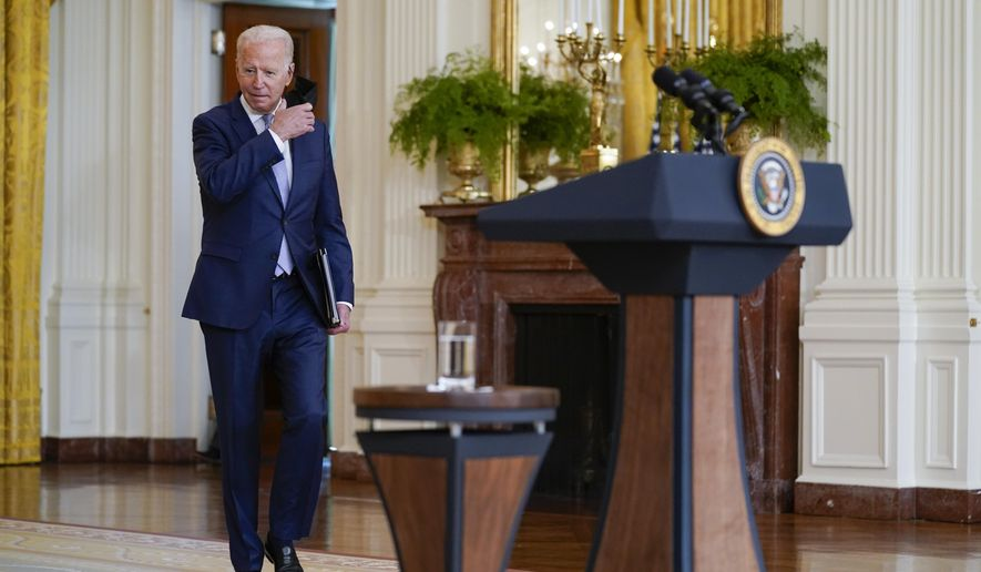 President Joe Biden removes his face mask as he arrives to speak in the East Room of the White House, Thursday, Aug. 12, 2021, in Washington. (AP Photo/Evan Vucci)