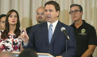 In this Aug. 10, 2021, file photo, Florida Gov. Ron DeSantis answers questions related to school openings and the wearing of masks in Surfside, Fla. Top Republicans are battling school districts in their own states' urban, heavily Democratic areas over whether students should be required to mask up as they head back to school. (AP Photo/Marta Lavandier) ** FILE **