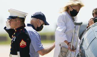 President Joe Biden helps first lady Jill Biden as they board Marine One to depart Delaware Air National Guard Base in New Castle, Del., Friday, Aug. 13, 2021. (AP Photo/Manuel Balce Ceneta)