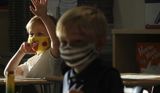 First Graders Alex Albin, left, and Tyler Custodio wear masks in Amanda McCoy's first grade class at the newly-rebuilt Addison Mizner School in Boca Raton, Tuesday, Aug. 10, 2021. Palm Beach County Schools opened the school year with a masking requirement with an opt-out option. (Joe Cavaretta/South Florida Sun-Sentinel via AP)