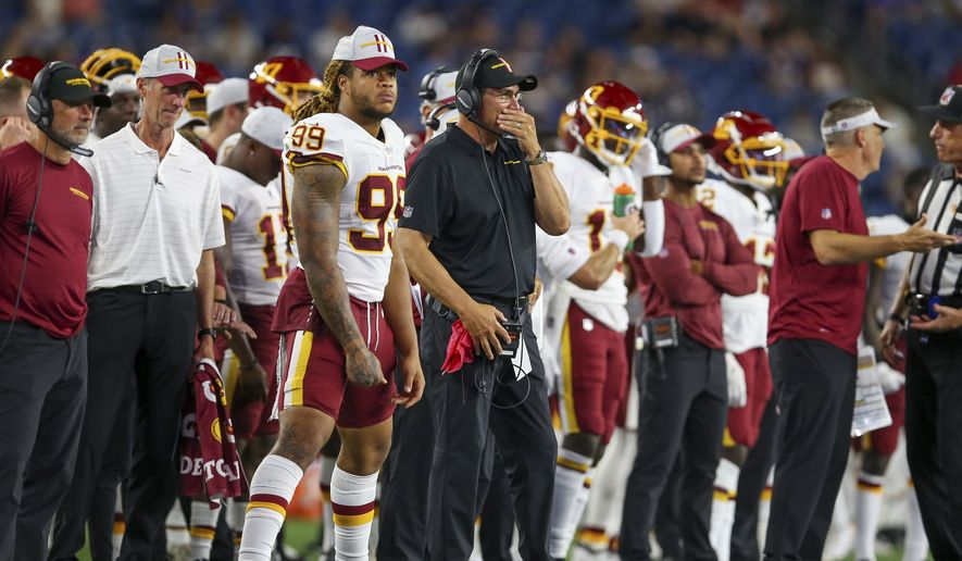 Washington Football Team defensive end Chase Young (99) and head coach Ron Rivera on the sideline during the second half of an NFL preseason football game against the New England Patriots, Thursday, Aug. 12, 2021, in Foxborough, Mass. (AP Photo/Stew Milne) **FILE**