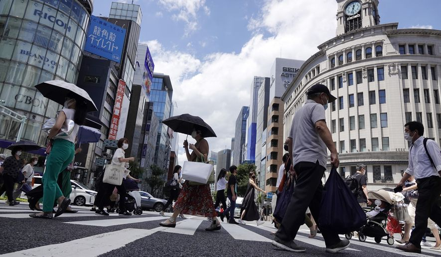 In this Aug. 10, 2021, file photo, people wearing face masks to help curb the spread of the coronavirus walk under the scorching sun in the Ginza Shopping district in Tokyo. Japan's Prime Minister Yoshihide Suga is pinning his hopes on vaccinations, which started slow but are now making good progress. How this race between shots and disease turns out may determine Suga's political future, not to mention the health of tens of thousands. (AP Photo/Eugene Hoshiko, File)