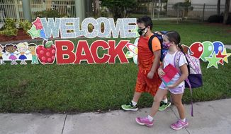 """FILE - In this Tuesday, Aug. 10, 2021 file photo, Students wearing protective masks walk past a """"Welcome Back"""" sign before the first day of school at Sessums Elementary School in Riverview, Fla. Students are required to wear the masks at school unless their parents opt out. President Joe Biden has called school district superintendents in Florida and Arizona, praising them for doing what he called """"the right thing"""" after their respective boards implemented mask requirements in defiance of their Republican governors amid growing COVID-19 infections. (AP Photo/Chris O'Meara, File)"""