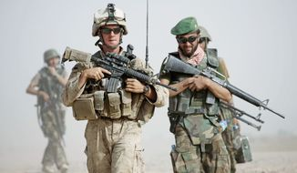 A U.S. Marine squad leader patrols alongside an Afghan National Army lieutenant in Helmand province in Afghanistan; the year is 2012. (Associated Press, FILE)