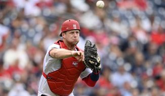 Washington Nationals catcher Riley Adams throws to first to put out Atlanta Braves' Austin Riley during the ninth inning of a baseball game, Sunday, Aug. 15, 2021, in Washington. (AP Photo/Nick Wass)