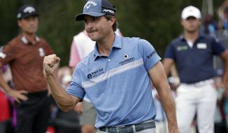 Kevin Kisner celebrates after making a birdie putt on the second playoff hole on the 18th green to win the Wyndham Championship golf tournament at Sedgefield Country Club in Greensboro, N.C., Sunday, Aug. 15, 2021. Other players, background, in the playoff look on. (AP Photo/Chris Seward) **FILE**