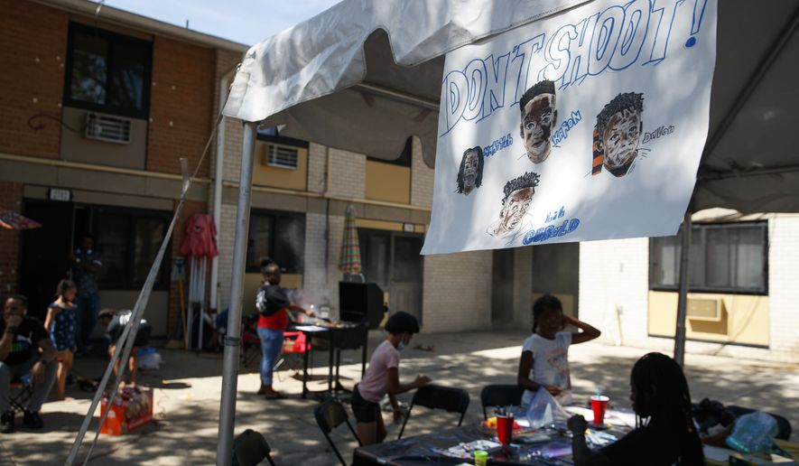"""A sign honoring Makiyah Wilson, 10, Karon Brown, 11, Davon McNeal, 11, and Gerald Watson, 15, who were all killed due to gun violence, is seen above an art activity booth during """"Don't Shoot DC"""" an event organized by Ar'Dinay Blocker, 18, Rontrell Haigler, 18, Laila Butler, 12, and Ja'Kyrah Cureton, 17, to give the youth a fun afternoon after enduring recent gun violence in their community, Thursday, July 23, 2020, in Washington. """"I have a 12 year old brother,"""" says Blocker, """"and he has already lost 3 friends to gun violence. So we wanted to give the kids something to make them feel like kids again."""" (AP Photo/Jacquelyn Martin)"""