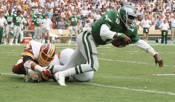 Philadelphia Eagles quarterback Randall Cunningham (12) is tripped up by Washington Redskins' linebacker Rich Milot (57) in first half action at RFK Stadium, Sept. 22, 1985. (AP Photo/Dennis Cook) **FILE**