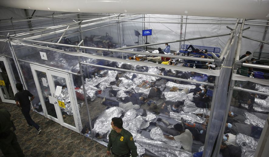 """In this March 30, 2021, file photo, young minors lie inside a """"pod"""" at the Donna Department of Homeland Security holding facility, the main detention center for unaccompanied children in the Rio Grande Valley. (AP Photo/Dario Lopez-Mills, Pool, File)"""