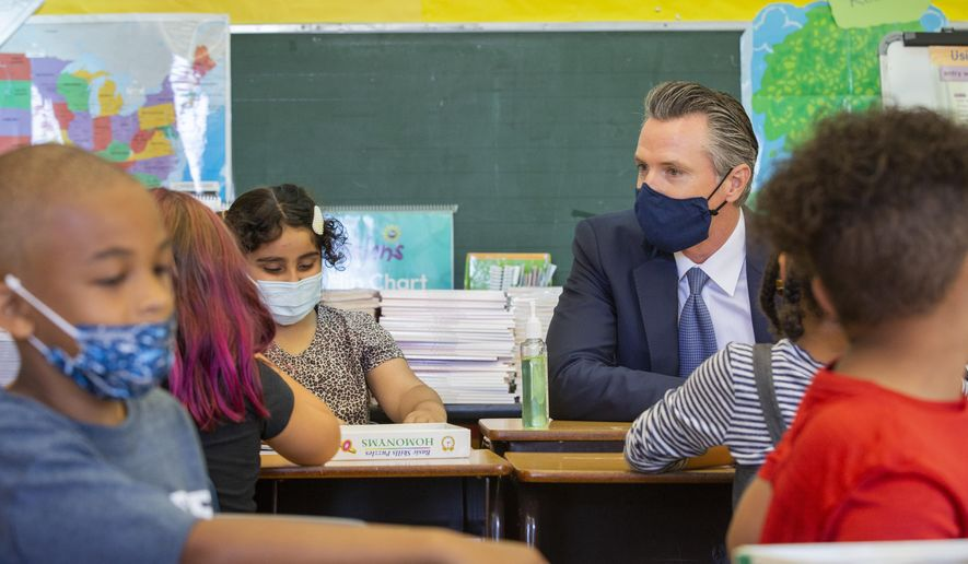 In this Aug. 11, 2021, file photo, California Gov. Gavin Newsom sits among students of a second-grade classroom at Carl B. Munck Elementary School, in Oakland, Calif.  (Santiago Mejia/San Francisco Chronicle via AP, Pool, File) **FILE**