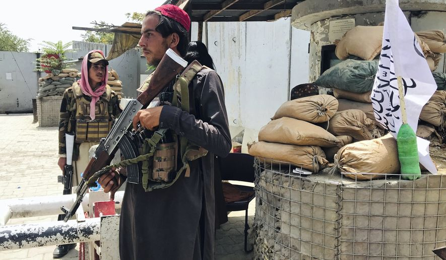 """Taliban fighters stand guard at a checkpoint near the US embassy that was previously manned by American troops, in Kabul, Afghanistan, Tuesday, Aug. 17, 2021. The Taliban declared an """"amnesty"""" across Afghanistan and urged women to join their government Tuesday, seeking to convince a wary population that they have changed a day after deadly chaos gripped the main airport as desperate crowds tried to flee the country. (AP Photo)"""