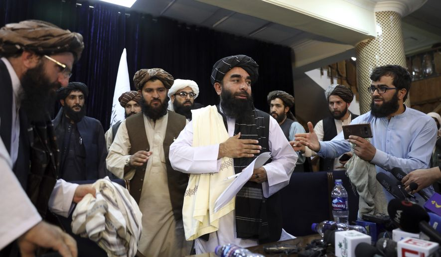 Taliban spokesman Zabihullah Mujahid, center, leaves after his first news conference, in Kabul, Afghanistan, Tuesday, Aug. 17, 2021. Mujahid vowed Tuesday that the Taliban would respect women's rights, forgive those who resisted them and ensure a secure Afghanistan as part of a publicity blitz aimed at convincing world powers and a fearful population that they have changed. (AP Photo/Rahmat Gul)