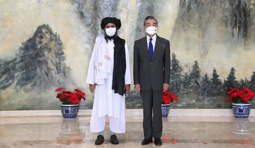 In this  July 28, 2021, file photo released by China's Xinhua News Agency, Taliban co-founder Mullah Abdul Ghani Baradar, left, and Chinese Foreign Minister Wang Yi pose for a photo during their meeting in Tianjin, China.  (Li Ran/Xinhua via AP, File)  **FILE**