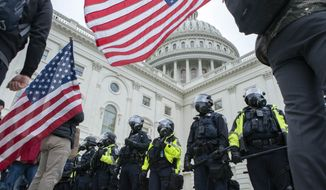 U.S. Capitol police push back supporters of President Donald Trump who try to break a door on the West side of the U.S. Capitol on Wednesday, Jan. 6, 2021, in Washington. (AP Photo/Jose Luis Magana)