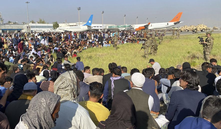 U.S soldiers stand guard along a perimeter at the international airport in Kabul, Afghanistan, Monday, Aug. 16, 2021. On Monday, the U.S. military and officials focus was on Kabul's airport, where thousands of Afghans trapped by the sudden Taliban takeover rushed the tarmac and clung to U.S. military planes deployed to fly out staffers of the U.S. Embassy, which shut down Sunday, and others. (AP Photo/Shekib Rahmani)