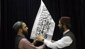 Taliban officials arrange a Taliban flag, before a press conference by Taliban spokesman Zabihullah Mujahid, at the Government Media Information Center, in Kabul, Afghanistan, Tuesday, Aug. 17, 2021. Mujahid vowed Tuesday that the Taliban would respect women's rights, forgive those who resisted them and ensure a secure Afghanistan as part of a publicity blitz aimed at convincing world powers and a fearful population that they have changed. (AP Photo/Rahmat Gul)