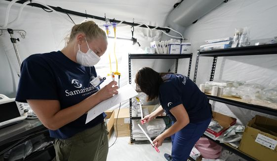 Nurse practitioners Taryn McCoy, left, and Gina LaFountain take inventory of supplies in the intensive care ward, one of four wards that are part of the 32-bed Samaritan's Purse Emergency Field Hospital set up in one of the University of Mississippi Medical Center's parking garages, Tuesday, Aug. 17, 2021, in Jackson, Miss. The field hospital joins a 20-bed field hospital and monoclonal antibody clinic opened by the U.S. Department of Health and Human Services at UMMC in response to the rising number of COVID-19 cases in the state. (AP Photo/Rogelio V. Solis) ** FILE **