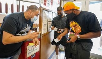 A Katz's Deli employee, left, checks the proof of vaccination from customers who will be eating inside the restaurant, Tuesday, Aug. 17, 2021, in New York. New York City is asking restaurants, gyms, museums and many other indoor venues to have patrons show proof of vaccination against COVID-19. The new rules are part of the city's latest campaign to control a pandemic that had crippled the city's economy. (AP Photo/Mary Altaffer)