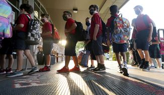Wearing masks to prevent the spread of COVID-19, elementary school students line up to enter school for the first day of classes in Richardson, Texas, Tuesday, Aug. 17, 2021. Despite Texas Gov. Greg Abbott's executive order banning mask mandates by local officials, the Richardson Independent School District and many others across the state are requiring masks for students. (AP Photo/LM Otero)