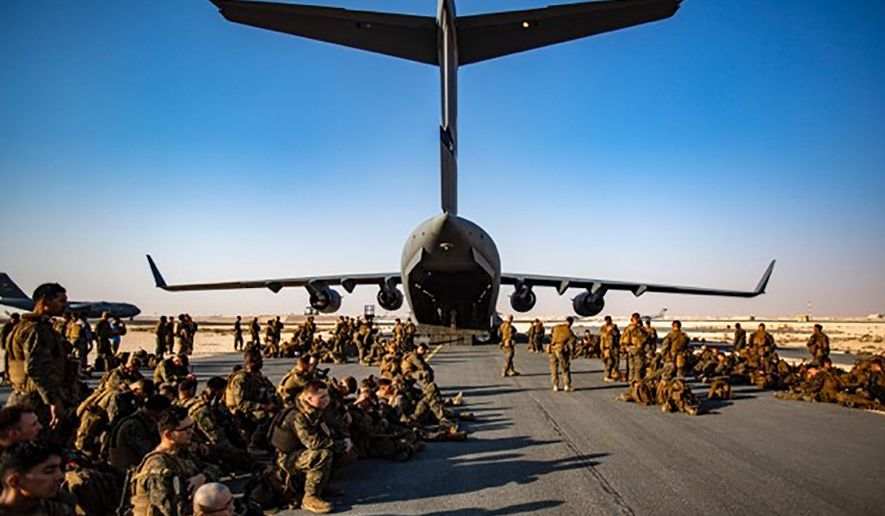 Marines assigned to the 24th Marine Expeditionary Unit (MEU) await a flight to Kabul Afghanistan, at Al Udeied Air Base, Qatar Tuesday, Aug. 17, 2021. Marines are assisting the Department of State with a drawdown of designated personnel in Afghanistan. (1st Lt. Mark Andries/U.S. Marine Corps via AP)