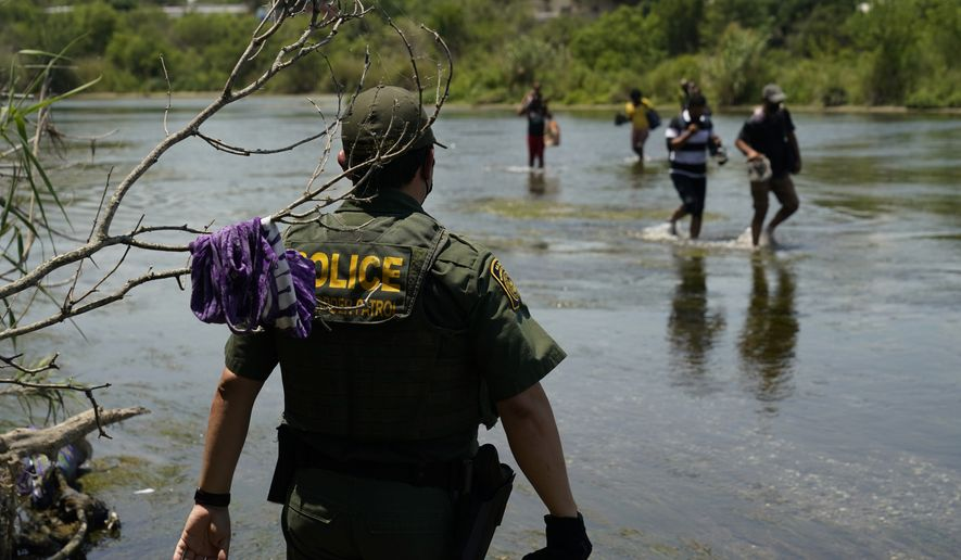 In this June 15, 2021, file photo a Border Patrol agent watches as a group of migrants walk across the Rio Grande on their way to turn themselves in upon crossing the U.S.-Mexico border in Del Rio, Texas. (AP Photo/Eric Gay, File)