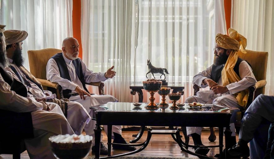In this handout photograph released by the Taliban, former Afghan President Hamid Karzai, center left, senior Haqqani group leader Anas Haqqani, right, meet in Kabul, Afghanistan, Wednesday, Aug. 18, 2021. The meeting comes after the Taliban's lightning offensive saw the militants seize the capital, Kabul. (Taliban via AP)