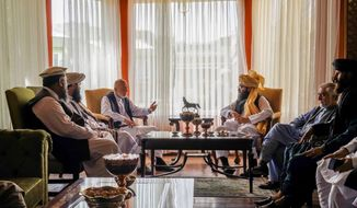 In this handout photograph released by the Taliban, former Afghan President Hamid Karzai, center left, senior Haqqani group leader Anas Haqqani, center right, Abdullah Abdullah, second right, head of Afghanistan's National Reconciliation Council and former government negotiator with the Taliban, and others in the Taliban delegation, meet in Kabul, Afghanistan, Wednesday, Aug. 18, 2021. The meeting comes after the Taliban's lightning offensive saw the militants seize the capital, Kabul. (Taliban via AP)  **FILE**