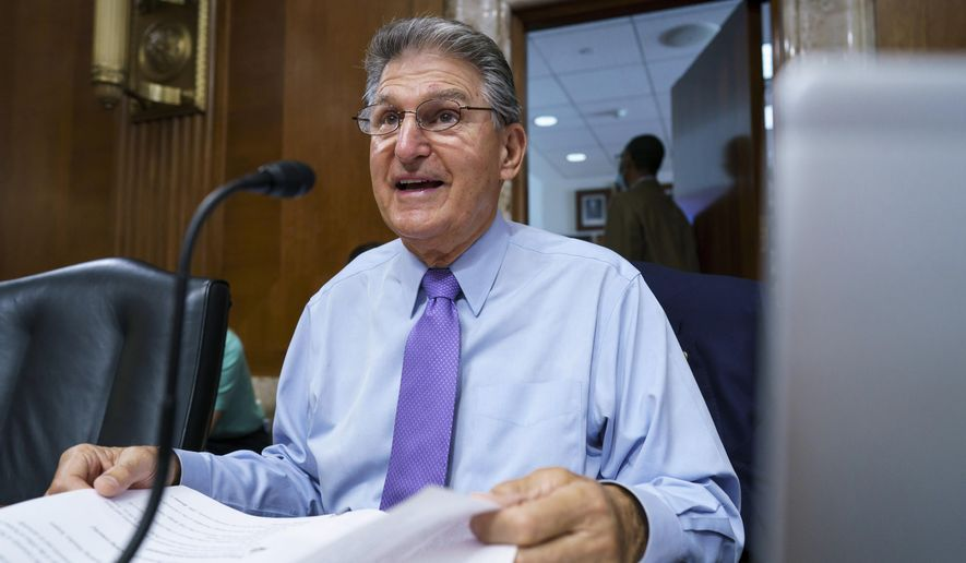 In this Aug. 5, 2021 photo, Sen. Joe Manchin, D-W.Va., prepares to chair a hearing in the Senate Energy and Natural Resources Committee, as lawmakers work to advance the $1 trillion bipartisan bill, at the Capitol in Washington. (AP Photo/J. Scott Applewhite)