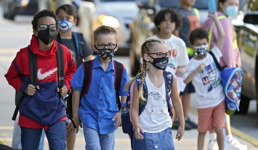 """FILE - In this Tuesday, Aug. 10, 2021 file photo, Students, some wearing protective masks, arrive for the first day of school at Sessums Elementary School in Riverview, Fla. President Joe Biden has called school district superintendents in Florida and Arizona, praising them for doing what he called """"the right thing"""" after their respective boards implemented mask requirements in defiance of their Republican governors amid growing COVID-19 infections. (AP Photo/Chris O'Meara, File)"""