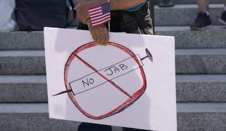 """A sign that reads """"No Jab"""" is held by a person taking part in a demonstration opposing mask and COVID-19 vaccine mandates outside the Legislative Building, Wednesday, Aug. 18, 2021, at the Capitol in Olympia, Wash. Washington Gov. Jay Inslee announced Wednesday that Washington state is expanding its vaccine mandate to include all public, charter and private school teachers and staff, as well as those working at the state's colleges and universities. Inslee also expanded the statewide indoor mask mandate in place for non-vaccinated individuals to include those who are vaccinated. (AP Photo/Ted S. Warren)"""