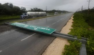 A road sign brought down by the winds of Hurricane Grace straddles one lane of a highway in Tulum, Quintana Roo state, Mexico, Thursday, Aug. 19, 2021. The Category 1 storm made landfall at 4:45 a.m., just south of the ancient Mayan temples of Tulum, pelting the Caribbean coast with heavy rain and pushing a dangerous storm surge. (AP Photo/Marco Ugarte)