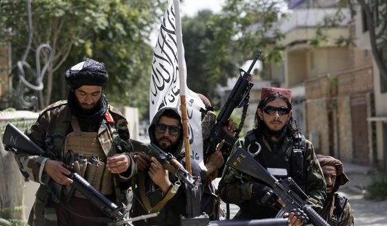 In this Aug. 19, 2021, photo, Taliban fighters display their flag on patrol in Kabul, Afghanistan. (AP Photo/Rahmat Gul)