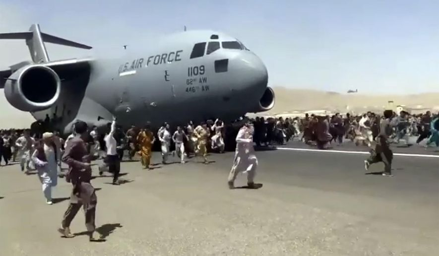 In this Aug. 16, 2021, file photo, hundreds of people run alongside a U.S. Air Force C-17 transport plane as it moves down a runway of the international airport, in Kabul, Afghanistan. (Verified UGC via AP, File)