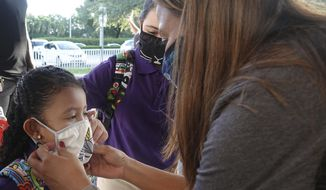 Dolphin Bay Elementary School kindergarten student Isabela Osorio gets an assist with her mask from her sister Valentina and Assistant Principal Janet Blano Soto, Wednesday, Aug. 16, 2021, in Miramar, Fla. More than 261,000 Broward County Public Schools (BCPS) students headed back to school to begin the 2021/22 school year. (Joe Cavaretta/South Florida Sun-Sentinel via AP)