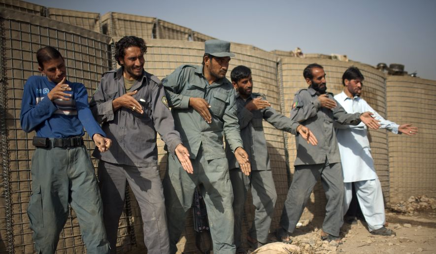 In this file photo from October 2010, Afghan policemen simulate weapons orientation during a training session with U.S. soldiers from 2nd PLT Diablos 552nd Military Police Company, on the outskirts of Kandahar City, Afghanistan. (AP Photo/Rodrigo Abd) ** FILE **
