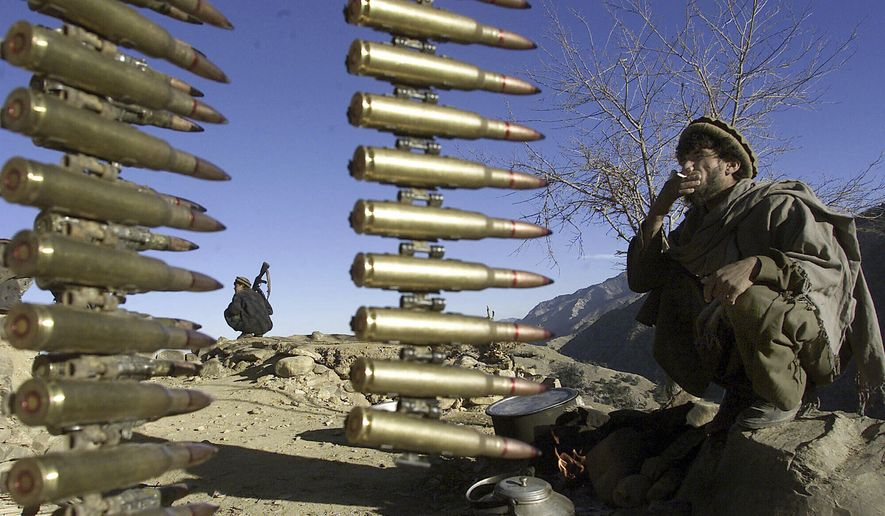 Afghan anti-al-Qaeda fighters rest at a former al Qaeda base in the White Mountains near Tora Bora on Wednesday, Dec. 19, 2001, behind a string of ammunition found after the retreat of al-Qaida members from the area. (AP Photo/David Guttenfelder) ** FILE **