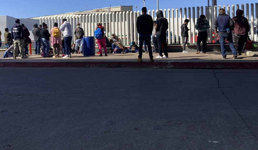 Migrants waiting to cross into the United States wait for news at the border crossing Wednesday, Feb. 17, 2021, in Tijuana, Mexico.  A federal appellate court refused late Thursday, Aug. 19 to delay implementation of a judges order reinstating a Trump administration policy forcing thousands to wait in Mexico while seeking asylum in the U.S. President Joe Biden had suspended former President Donald Trumps Remain in Mexico policy on his first day in office and the Department of Homeland Security said it was permanently terminating the program in June, according to the court record.  (AP Photo/Elliot Spagat) **FILE**