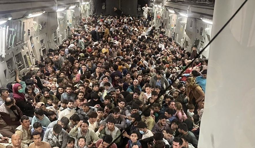 Afghan citizens pack inside a U.S. Air Force C-17 Globemaster III, as they are transported from Hamid Karzai International Airport in Afghanistan, Sunday, Aug. 15, 2021. (Capt. Chris Herbert/U.S. Air Force via AP)
