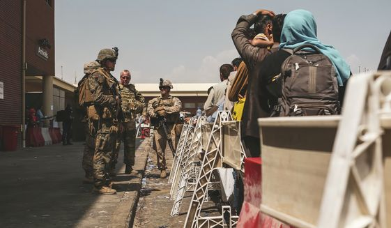 In this image provided by the U.S. Marine Corps, Marines assigned to the 24th Marine Expeditionary Unit (MEU) provide assistance during an evacuation at Hamid Karzai International Airport in Kabul, Afghanistan, Friday, Aug. 20, 2021. (Sgt. Isaiah Campbell/U.S. Marine Corps via AP)