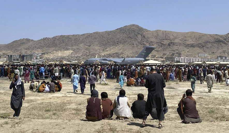 In this Monday, Aug. 16, 2021, file photo hundreds of people gather near a U.S. Air Force C-17 transport plane along the perimeter at the international airport in Kabul, Afghanistan. Hundreds of Western nationals and Afghan workers have been flown to safety since the Taliban reasserted control over the country. Yet still unprotected, and in hiding, are untold numbers of Afghans who tried to build a fledgling democracy. They include Afghans who worked with foreign forces, and who are now stranded and being hunted by the Taliban, along with aid workers. (AP Photo/Shekib Rahmani, File)